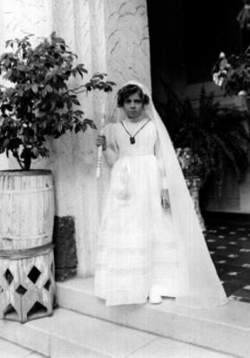 Niña con traje de primera comunión posando en un pasillo, retrato