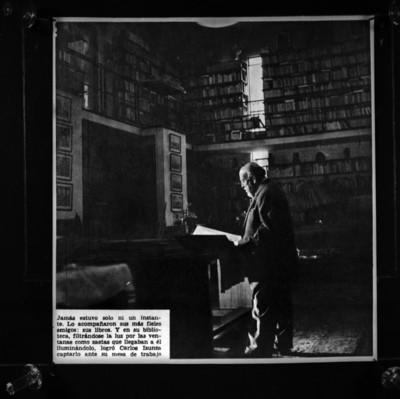 Alfonso Reyes leyendo libros en su biblioteca