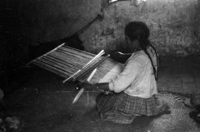 Mujer indNBigena sentada frente a su telar