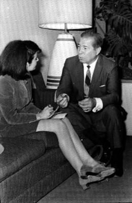 Mujer entrevista a hombre en una habitación