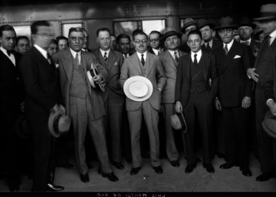 Luis Montes de Oca acompañado por varios hombres junto a un tren en una estación, retrato e grupo