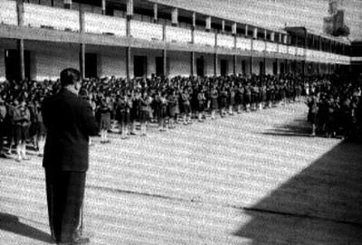 Niños escuchan discurso en patio cívico de una escuela