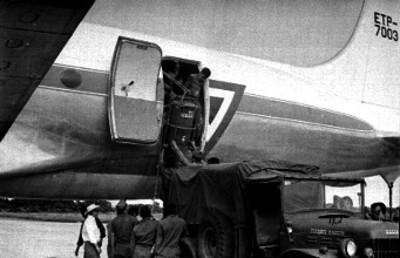 Trabajadores descargan tambos de un avión