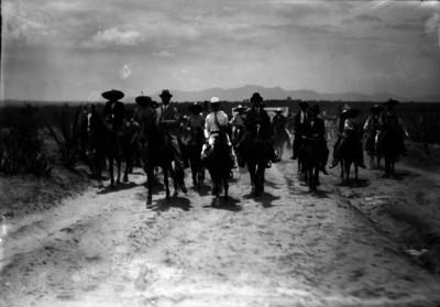 David Montes de Oca a caballo con partidarios en el camino de un poblado durante su campaña electoral