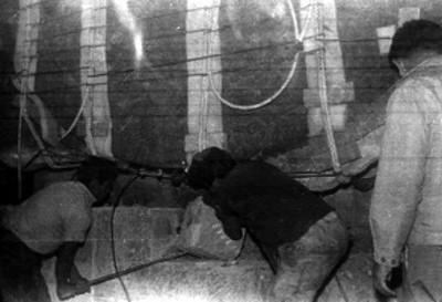 Hombres manipulan maquinaria hidráulica para descargar la Piedra del Sol