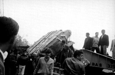 Hombres observan maniobras del vehículo que porta la Piedra del Sol
