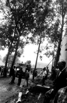 Hombres observan llegada del vehículo que transporta la piedra del Sol, en las afueras del museo