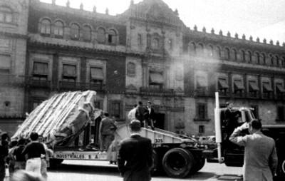 Gente observa la Piedra del Sol a su paso por el Zócalo de la ciudad de México