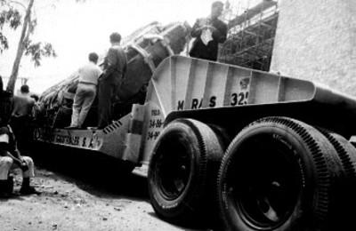 Hombres junto a la Piedra del Sol sobre plataforma de trailer estacionado en una calle