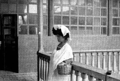 Mujer de pie y de perfil, recargada en barandal