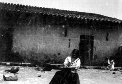 Mujer indígena teje sobre un telar en el patio de una casa