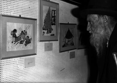 Gerardo Murillo, pintor observando sus pinturas en una exposición