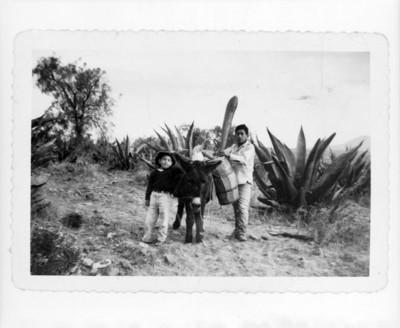 Tlachiquero acompañado de niño en un camino rural