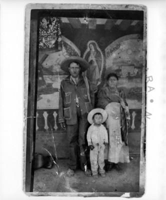 Familia de pie, frente a una imagen de la Virgen de Guadalupe