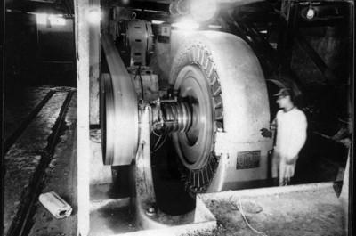 Obreros junto a maquinaria generadora de electricidad en la fábrica de papel, vista interior