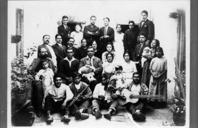 Familia con músicos en el patio de una casa, retrato de grupo