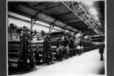 Hombres junto a cilindros de maquinaria industrial, interior de fábrica