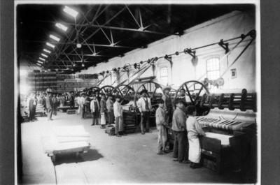 Hombres manipulan maquinaria en el interior de la fábrica