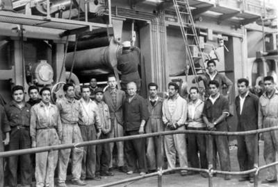 Trabajadores de la fábrica de papel cerca de maquinaria, retrato de grupo