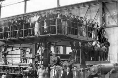 Hombres recargados sobre barandal dentro de la fábrica, retrato de grupo