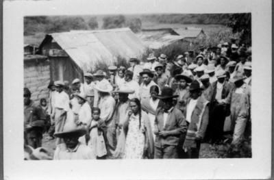 Campesinos caminan en hilera en calle de poblado