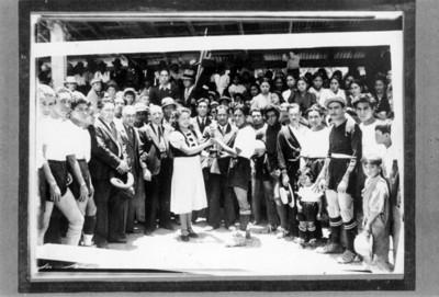 Mujer entrega premio a futbolista durante festejo, retrato de grupo