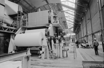 Trabajadores en interior de la fábrica San Rafael junto a bobinadora de papel