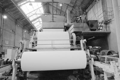 Obreros operan en máquina bobinadora de papel, fábrica San Rafael