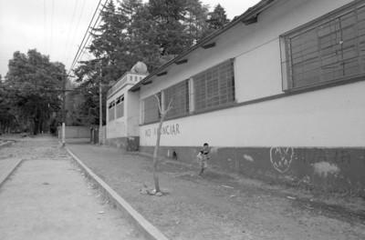 Niño camina en banqueta en calle del poblado de San Rafael