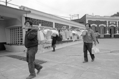 Obreros cargan su almuerzo en garrocha