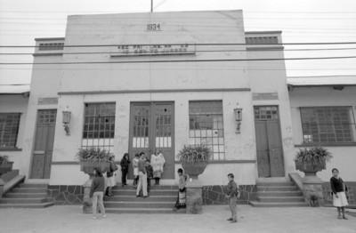"""Personas paradas a la entrada de """"Escuela Benito Juárez"""", vista frontal"""