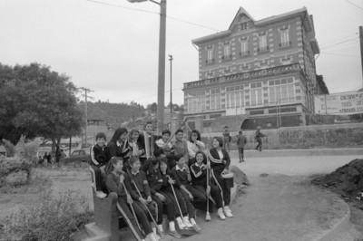 Estudiantes sentados en una banca de jardín, al fondo el antiguo Casino-Hotel de la fábrica San Rafael