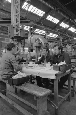 Obreros trabajan en un mesabanco junto a maquinaria