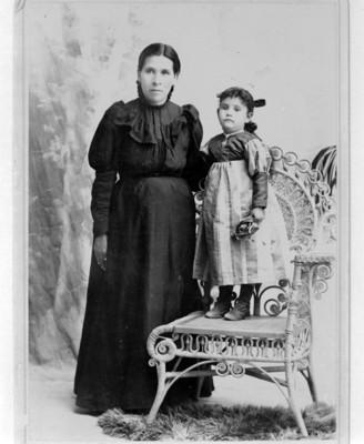 Mujer y niña sobre silla posan para retrato