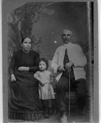 Hombre y mujer sentados posan junto a niña, retrato de grupo
