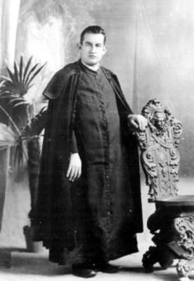 Hombre con vestimenta eclesiástica posa de pie recargado en silla