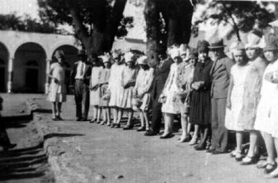 Muchachas y jóvenes posan hacia la cámara en la calle, retrato de grupo