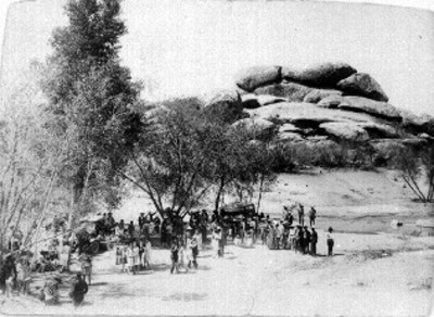 Gente convive durante día de campo, cerca de una peña