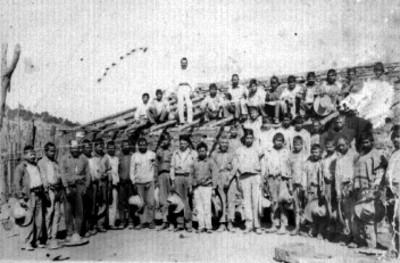 Hombres reunidos sobre construcción de madera y adobe, retrato de grupo