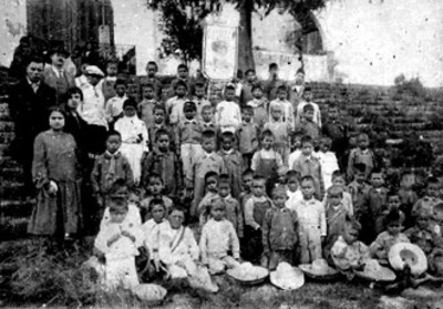 Niños y niñas reunidos con maestros posan para fotografía escolar, retrato de grupo