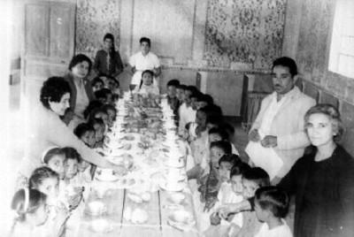 Niños y niñas sentados desayunan sobre mesa larga, retrato de grupo