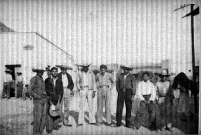 Hombres posan en calle de poblado, retrato de grupo