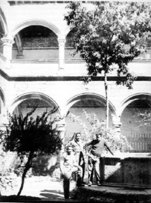Tres hombres posan junto a fuente en patio interior del claustro de San Andrés