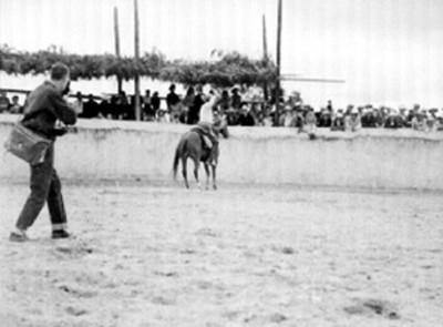Hombre vestido de charro monta a caballo sobre rodeo
