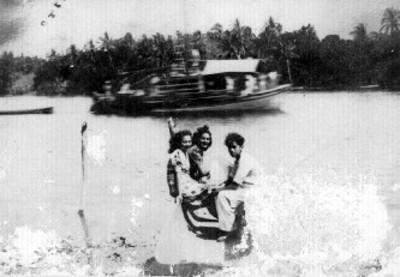 Mujeres en el muelle y embarcación al fondo