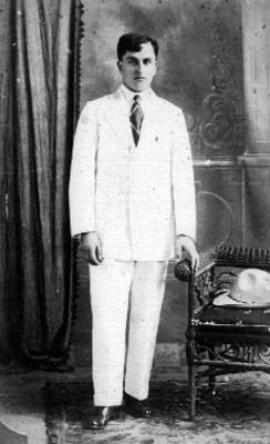 Hombre de pie viste traje blanco y posa para fotografía, retrato