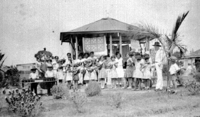 Grupo de niños tocan instrumentos musicales cerca de un kiosko, retrato