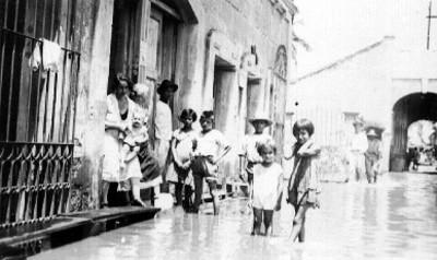 Mujer con niños salen de casa hacia calle inundada