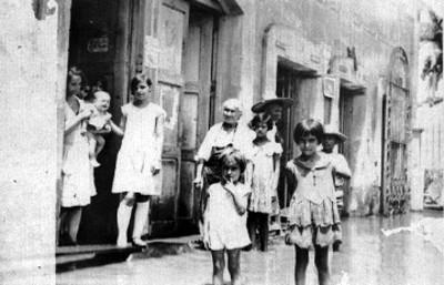 Familia afuera de una casa con calle inundada, retrato de grupo