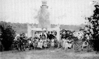 Gente reunida dentro de una carpa adornada bajo un faro, retrato de grupo